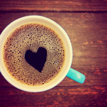 a cup of coffee with a heart shape toned with a retro vintage in